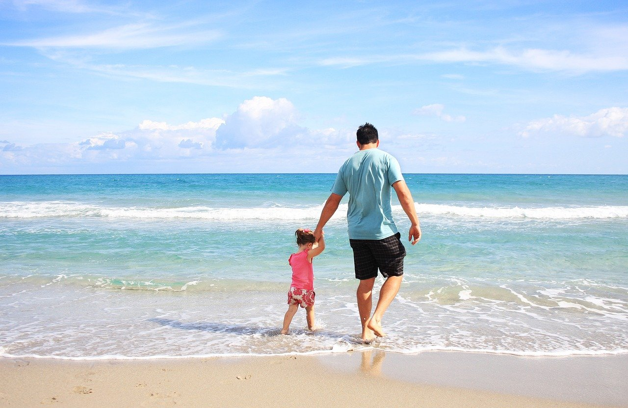 Father and Child on the beach - How To Travel Safely During The Pandemic